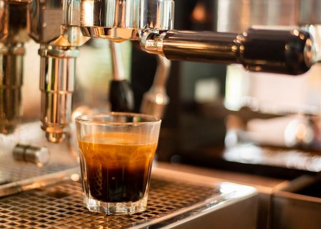 Cerca de la máquina de café está preparando café en la cafetería.