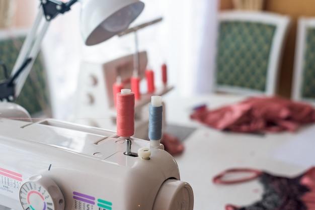 Cerca de la máquina de coser con bobinas de hilo de coral