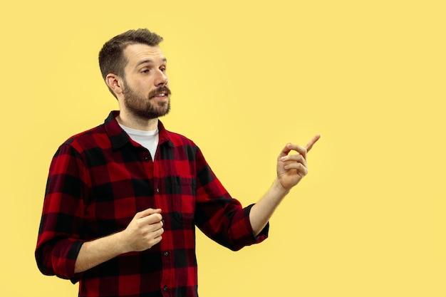 Cerca de medio cuerpo retrato de hombre joven en camisa en el espacio amarillo. las emociones humanas, el concepto de expresión facial. vista frontal. colores de moda. espacio negativo