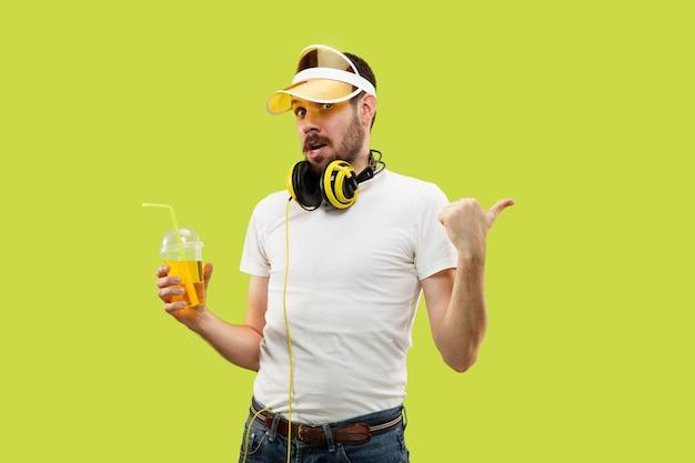 Cerca de medio cuerpo retrato de hombre joven en camisa en el espacio amarillo. modelo masculino con auriculares y bebida.