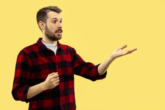 Cerca de medio cuerpo retrato de hombre joven en pared amarilla.