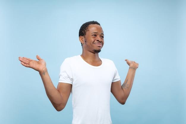Cerca de medio cuerpo retrato de joven afroamericano con camisa blanca en la pared azul. las emociones humanas, la expresión facial, el concepto publicitario. mostrando barra vacía, señalando, eligiendo, invitando.