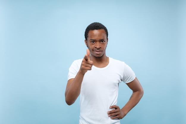 Cerca de medio cuerpo retrato de joven afroamericano con camisa blanca en la pared azul. las emociones humanas, la expresión facial, el concepto publicitario. señalar, elegir y sonreír. copyspace.