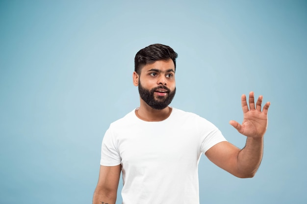 Cerca de medio cuerpo retrato de joven hindú con camisa blanca sobre fondo azul. las emociones humanas, la expresión facial, el concepto publicitario. espacio negativo. mostrando barra espaciadora vacía, señalando, saludando.