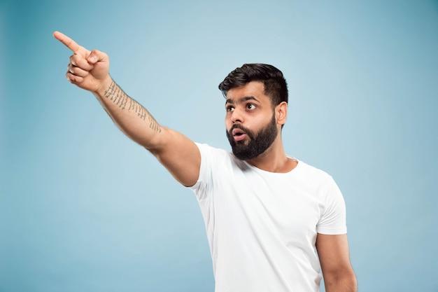 Cerca de medio cuerpo retrato de joven hindú con camisa blanca sobre fondo azul. las emociones humanas, la expresión facial, las ventas, el concepto publicitario. espacio negativo. señalando conmocionado y asombrado.
