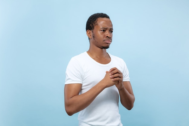 Cerca de medio cuerpo retrato de joven modelo masculino afroamericano en camisa blanca en la pared azul. las emociones humanas, la expresión facial, el concepto publicitario. dudas, preguntando, mostrando incertidumbre, pensativo.