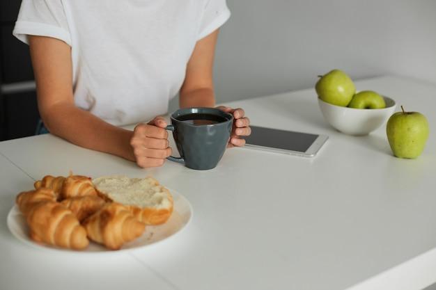 Cerca de la mesa de la cocina blanca con manos de mujer mantiene una taza gris con algo de líquido, croissants en un plato, manzanas en un recipiente