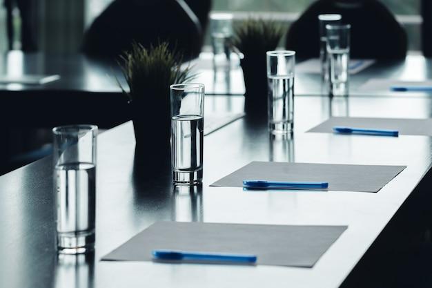 Cerca de la mesa de conferencias oscura vasos de agua plumas, hojas de papel