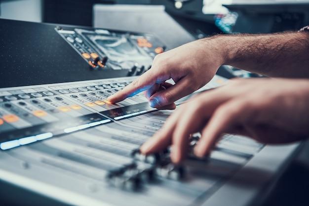 De cerca. mezclador en estudio de sonido de productor de sonido.