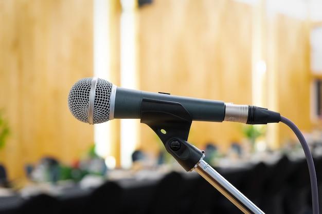 Cerca del micrófono al lado del podio con desenfoque de tiempo de cena de mesa larga y negra en luz cálida de tungsteno.