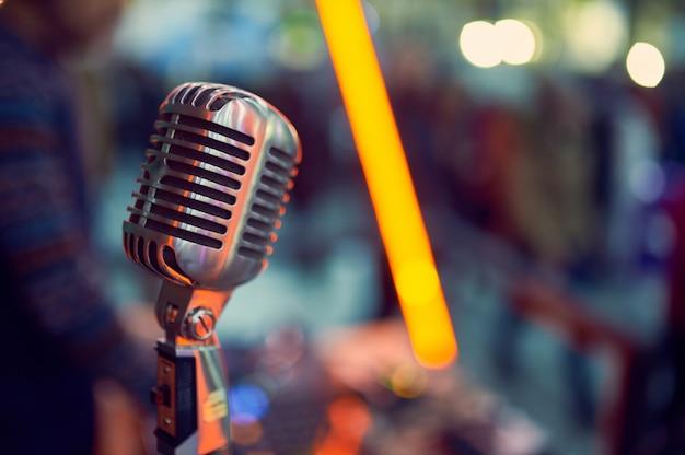 Cerca de un micrófono vintage profesional con luces borrosas