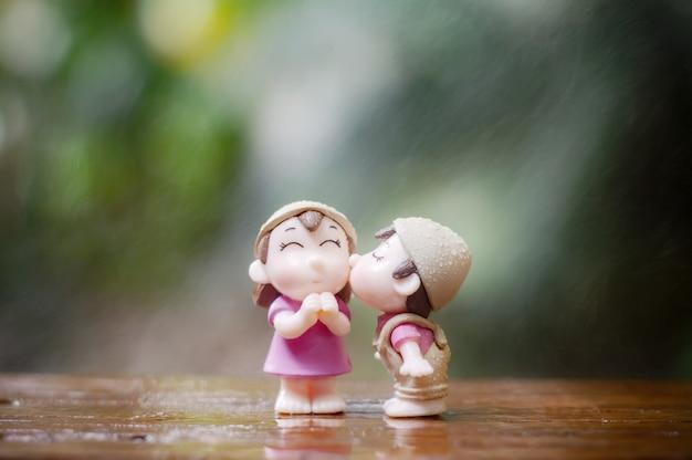 Cerca de mini muñecas pareja en beso romántico para el concepto de san valentín