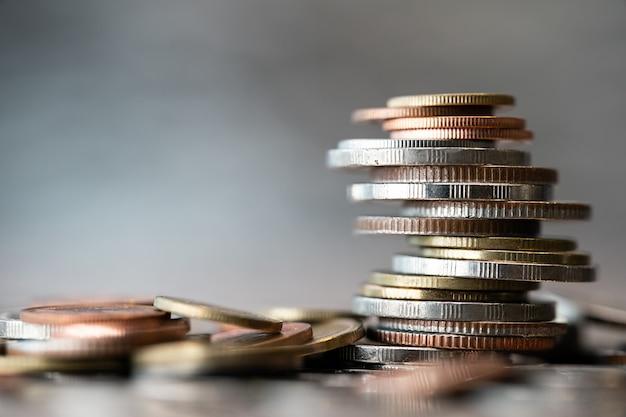 Cerca de monedas apiladas con otras en diferentes posiciones sobre fondo borroso.