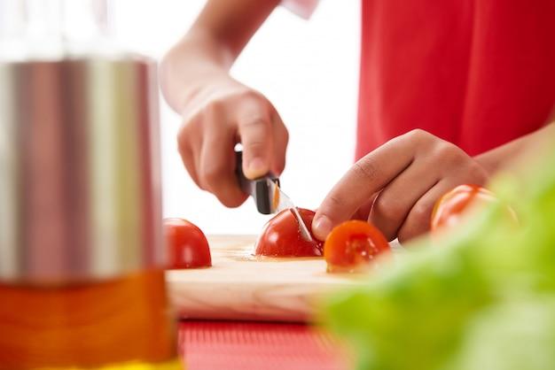 De cerca. la muchacha africana corta los tomates en tablero de la cocina.
