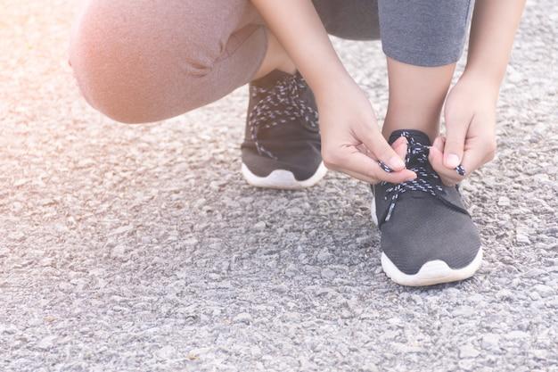 Cerca de la muchacha de la aptitud que ata su cordón del zapato y alista para correr