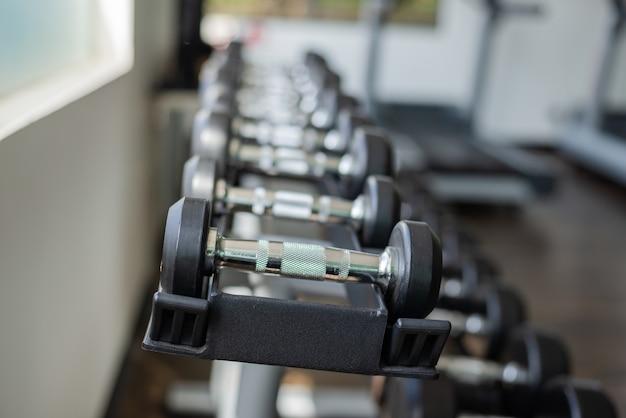 Cerca de muchas pesas en el gimnasio deportivo