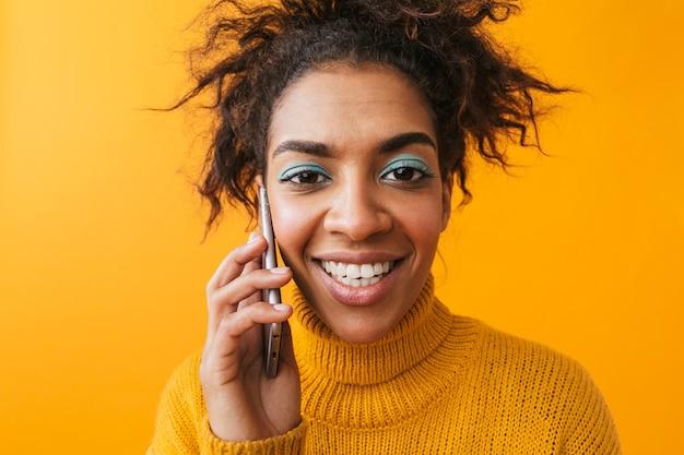 Cerca de una mujer africana confundida emocionada vistiendo suéter que se encuentran aisladas, hablando por teléfono móvil