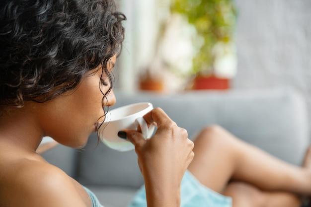 Cerca de mujer afroamericana en toalla haciendo su rutina diaria de belleza en casa. sentado en el sofá, luce satisfecho, tomando café y relajándose.