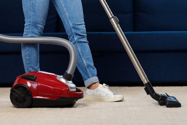 Cerca de una mujer aspirar la alfombra