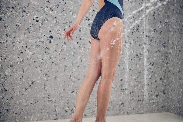 Cerca de una mujer caucásica en traje de baño recibiendo un masaje con agua a alta presión