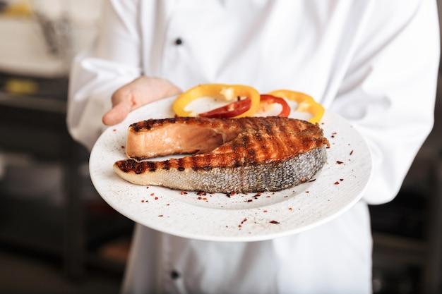 Cerca de una mujer chef cocinero con uniforme mostrando filete de salmón asado cocido mientras está de pie en la cocina