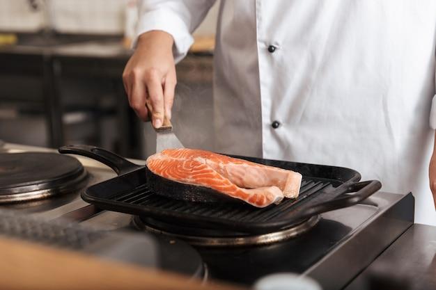 Cerca de una mujer chef cocinero vistiendo uniforme cocinando delicioso filete de salmón de pie en la cocina
