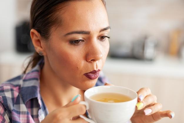 Cerca de la mujer en la cocina tratando de beber té verde caliente con hierbas aromáticas