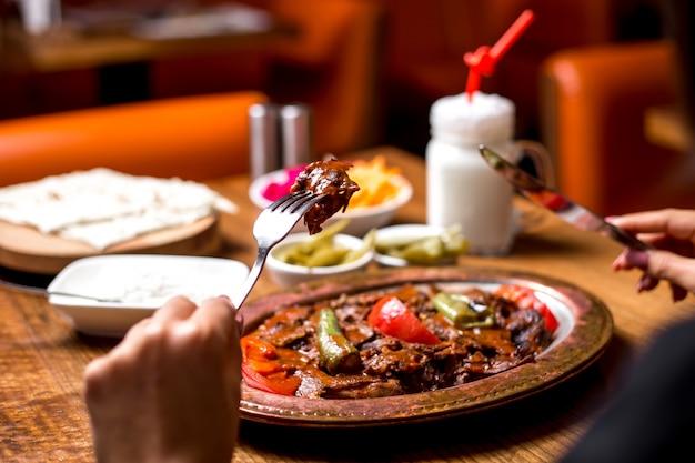 Cerca de mujer comiendo kebab iskender en bandeja de cobre con pepinillos yogur y ayran