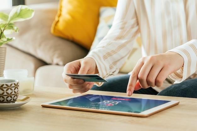 Cerca de una mujer de compras online con su tarjeta de crédito