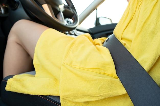 Cerca de mujer conductora en vestido amarillo de verano con cinturón de seguridad conduciendo un coche.