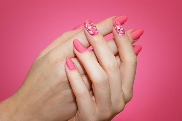 Cerca de las uñas de mujer cuidadas con arte de uñas rosa