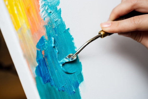 Cerca de mujer dibujando con pinturas al óleo sobre lienzo