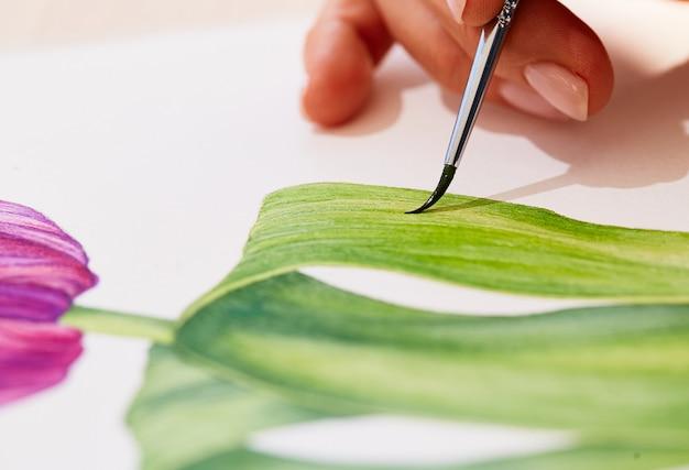 De cerca, la mujer está dibujando un tulipán