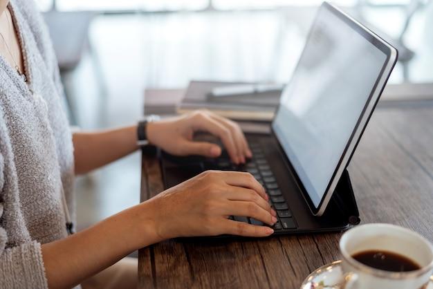 Cerca de la mujer diseñadora gráfica con tableta digital mientras trabaja