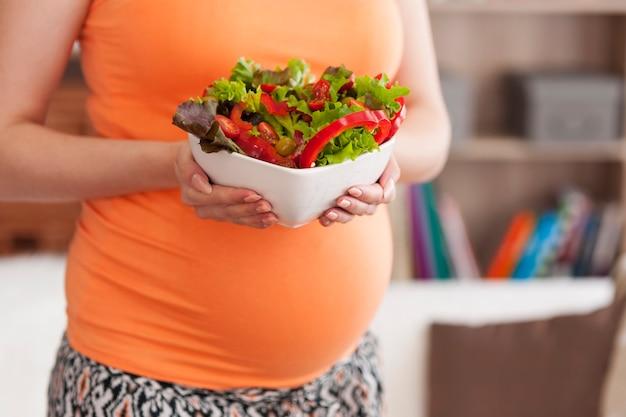 Cerca de la mujer embarazada con ensalada de verduras