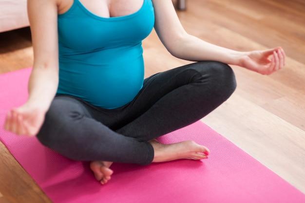 Cerca de la mujer embarazada durante el yoga
