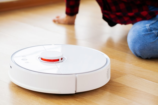 Cerca de la mujer enciende la aspiradora robot inteligente.