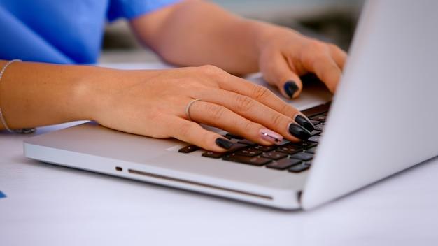 Cerca de la mujer enfermera escribiendo informe de salud del paciente en el teclado de la computadora portátil haciendo citas en la clínica médica, registro de pacientes. médico de la salud en tratamientos de escritura uniforme de medicina.
