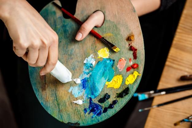 Cerca de mujer exprimiendo pintura de aceite blanco en la paleta