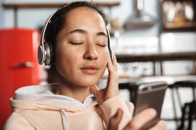 Cerca de una mujer feliz escuchando música con auriculares en casa