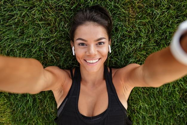 Cerca de una mujer feliz fitness en auriculares