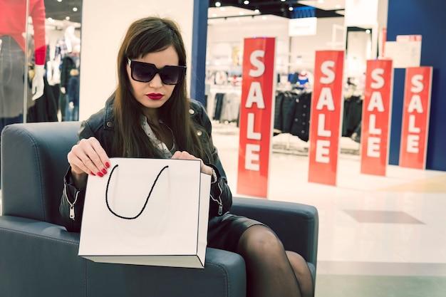 Cerca de la mujer con gafas oscuras sentado en el sillón del centro comercial y mirando a sus nuevas compras compradas en una venta. señora que abre el bolso de compras del papel blanco en fondo rojo de la venta de las banderas. descuentos estacionales
