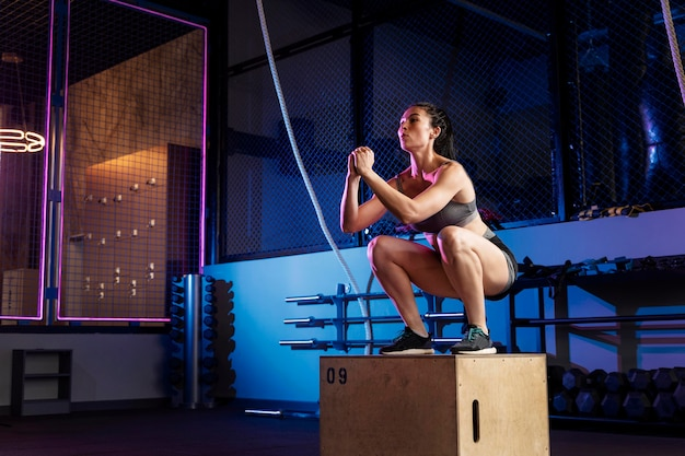 Cerca de mujer haciendo entrenamiento crossfit