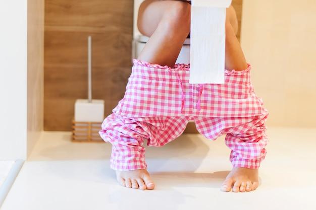 Cerca de la mujer en el inodoro en la mañana