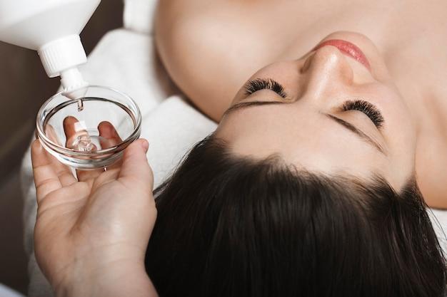 Cerca de una mujer joven con cabello oscuro apoyado en una cama de spa con los ojos cerrados, mientras que cerca de su rostro están las manos de la cosmetóloga poniendo máscara en un recipiente.