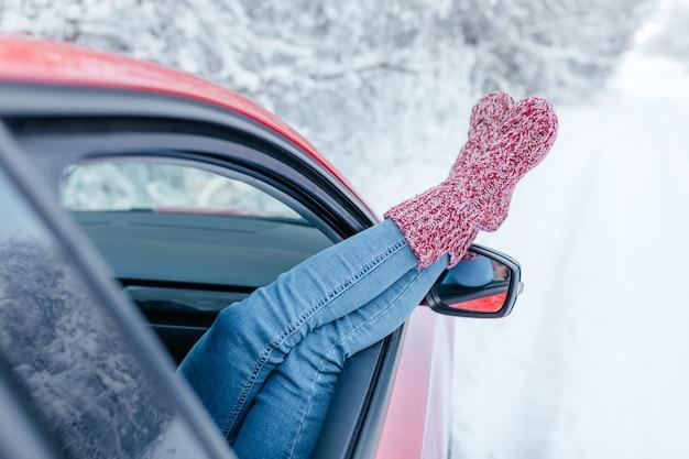 De cerca. mujer joven en calcetines calientes descansando dentro del coche.