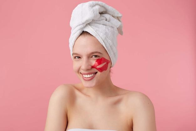 Cerca de una mujer joven feliz después del spa con una toalla en la cabeza, con un parche para los labios en las mejillas, se siente tan feliz, sonríe ampliamente, se para.