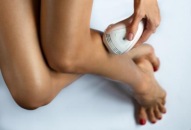 Cerca de una mujer joven con láser de cuerpo perfecto que depila sus piernas suaves y sedosas sin pelo