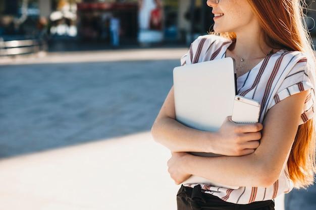 Cerca de una mujer joven manos sosteniendo una computadora portátil y un teléfono inteligente afuera contra un edificio.