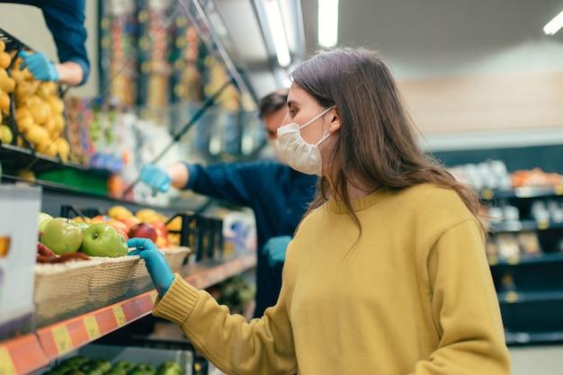 De cerca. mujer joven con una máscara protectora compra manzanas